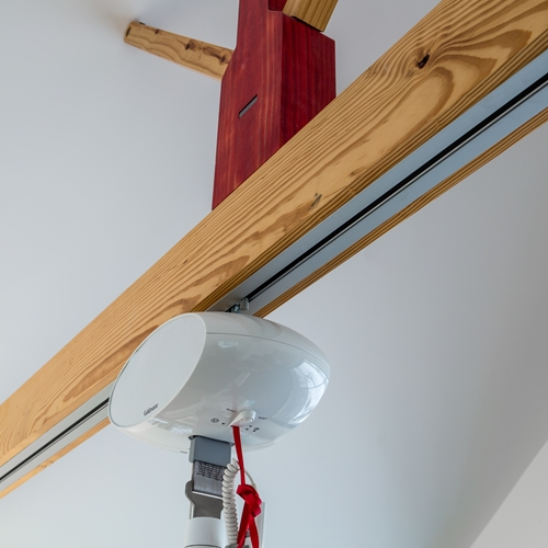 A GH1 ceiling hoist system is used in the client's bedroom with the rail system integrated subtly into an exposed timber beam, so that the practical aid is almost invisible.